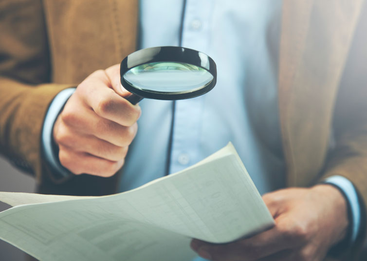 Real estate appraiser analyzing an appraisal report with a magnifying glass
