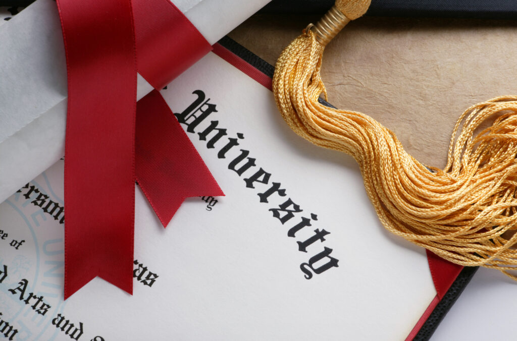 Gold tassel and rolled diploma with red ribbon